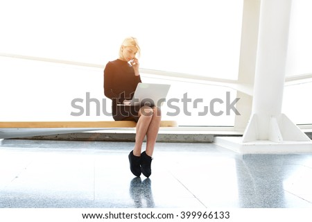Woman designer of websites is talking on mobile phone with customer, while is sitting with laptop computer in co-working space. Pretty female with net-book on knees having cell telephone conversation - stock photo