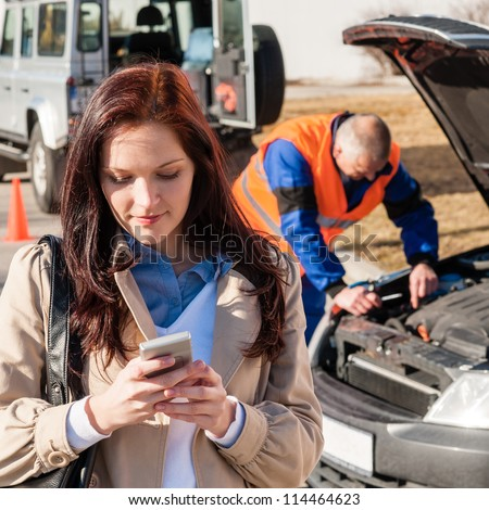 Woman dialing on cellphone after car breakdown accident crash problem - stock photo