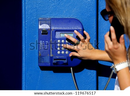 Woman dials for public pay phone outdoor - stock photo