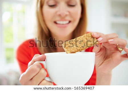 Woman Dipping Biscuit Into Hot Drink At Home - stock photo
