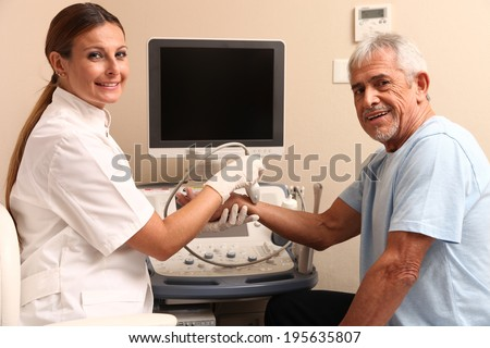 Woman doctor examing patient man wrist with ultrasound. - stock photo
