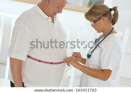 Woman doctor examining an obese patient. - stock photo