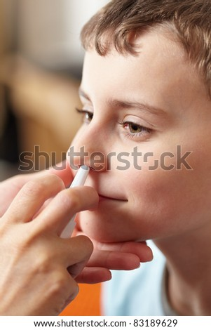 Woman doctor hands giving a boy a dose of nasal spray against flu - stock photo