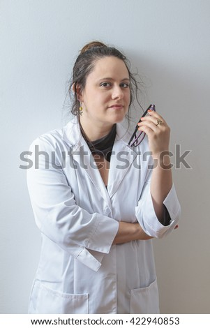 Woman doctor holding her glasses and leaning against a white wall - stock photo