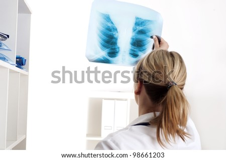 woman doctor looks at x-ray film, shot from behind - stock photo