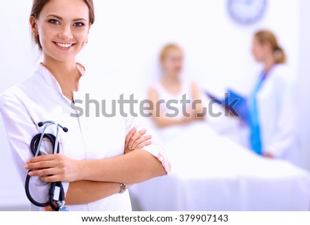 Woman doctor standing at hospital - stock photo