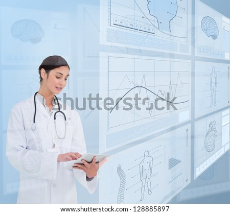 Woman doctor using a tablet pc near to futuristic screens - stock photo