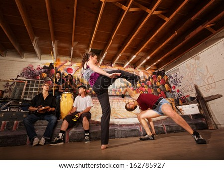Woman dodging a capoeira front kick indoors - stock photo