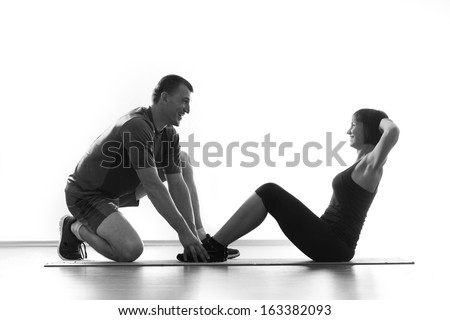 Woman does situps with coach in training gym abdominal silhouette studio isolated on white background - stock photo