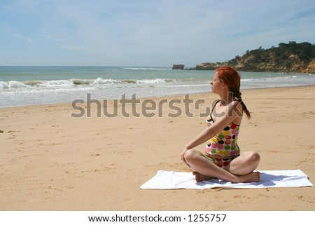 woman does yoga and meditation on beach - stock photo