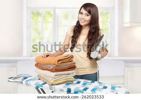 woman doing a housework holding laundry - stock photo