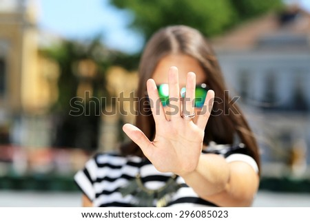 woman doing a stop gesture, outdoor - stock photo