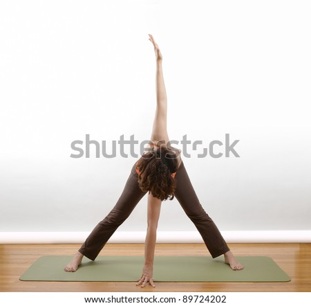 Woman doing an arm extension yoga pose om a green mat - stock photo