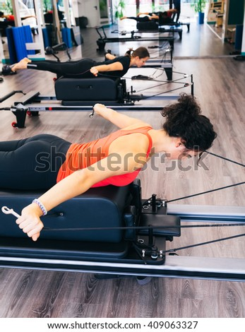 Woman doing back and arms exercises using a reformer bed  - stock photo
