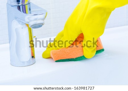 woman doing chores  in bathroom at home, cleaning sink and faucet  with spray detergent - stock photo