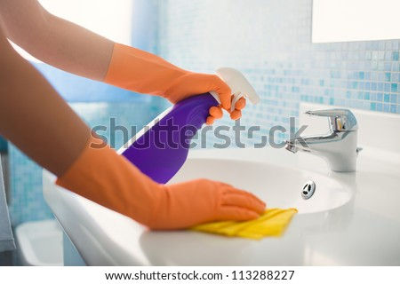 woman doing chores in bathroom at home, cleaning sink and faucet with spray detergent. Cropped view - stock photo