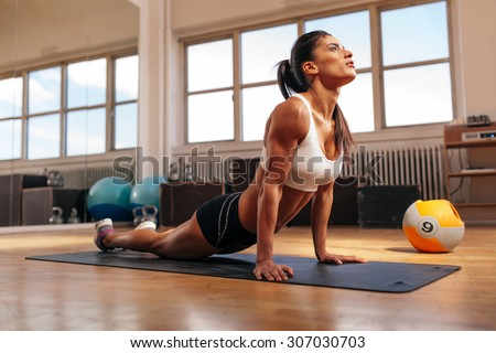 Woman doing core stretch on fitness mat. Muscular young woman doing stretching exercise in gym. - stock photo
