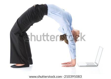 Woman doing crab yoga pose in studio. Woman exercising and looking at computer screen - stock photo