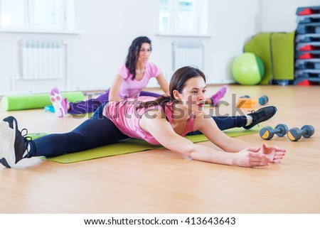Woman doing cross split exercise working out her hip abductor muscles and ligaments. Fit female athlete stretching splits in gym - stock photo