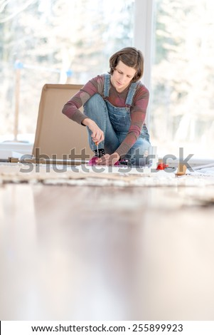 Woman doing DIY repairs at home kneeling on the floor in front of a bright glass window surrounded by materials and tools working with a screwdriver. Focus on the screwdriver. - stock photo