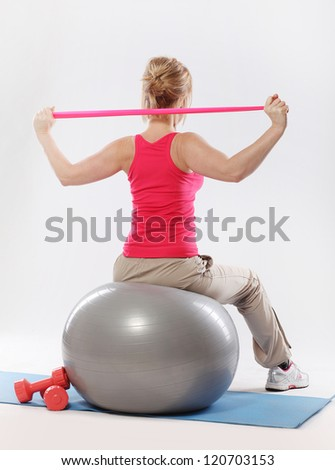Woman doing exercise with tape view from the back over a grey background - stock photo