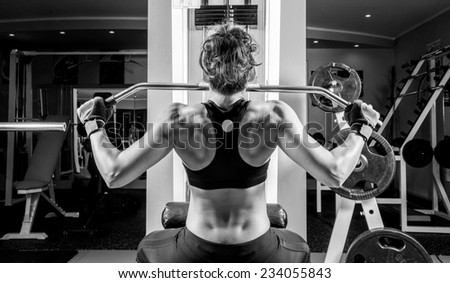 Woman doing fitness at the fitness centre. Black and white picture. - stock photo
