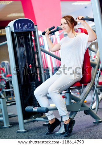 Woman doing fitness training on a butterfly machine with weights in a gym - stock photo