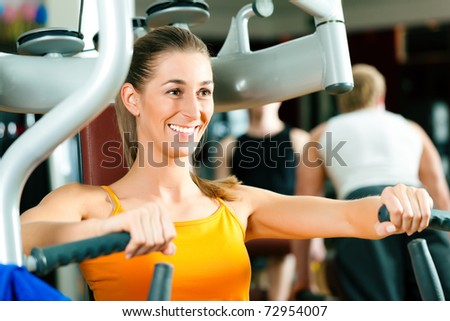Woman doing fitness training on a butterfly machine with weights in gym or fitness club - stock photo