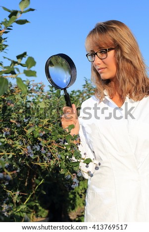Woman doing Food inspection quality control with magnifying glass - stock photo