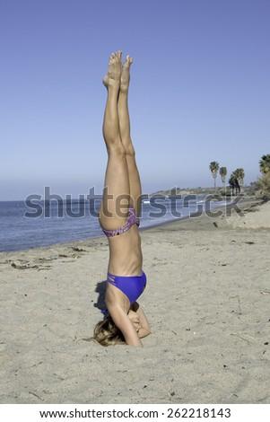 Woman doing her yoga on a beach/Beach Yoga/Woman working on her yoga on a California beach during the morning - stock photo