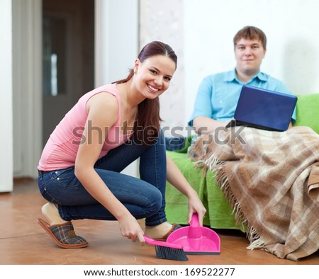 woman doing house cleaning during man rests over sofa - stock photo