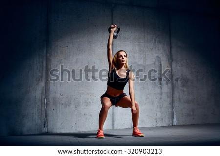 Woman doing Kettlebell Overhead Exercise - stock photo