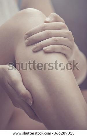 Woman doing leg massage and applying moisturizing cream - stock photo