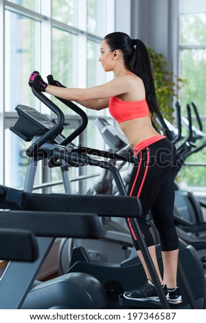 Woman doing legs exercise on stair steppers machine, in gym fitness center - stock photo