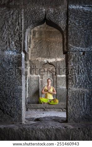 Woman doing meditation in the temple of Hampi, Karnataka, India - stock photo