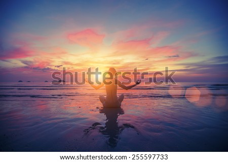 Woman doing meditation near the ocean beach. Yoga silhouette. - stock photo