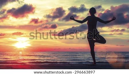 Woman doing meditation near the ocean beach. Yoga silhouette.  - stock photo
