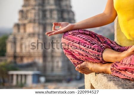 Woman doing meditation near Virupaksha temple in Hampi, Karnataka, India - stock photo
