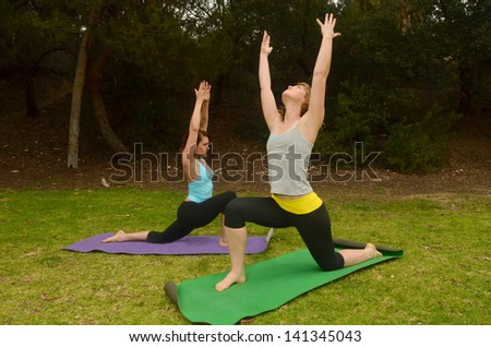 Woman doing outdoor yoga/Outdoor Yoga.Two woman are engaged in yoga in outdoor setting - stock photo
