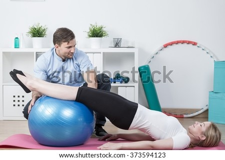 Woman doing physiotherapy exercises  with fitness ball  - stock photo