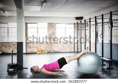 Woman doing pilates against gym - stock photo