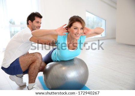 Woman doing pilates exercises with coach - stock photo