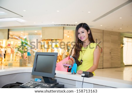 woman doing shopping in mall and paying by credit card at the pay desk - stock photo