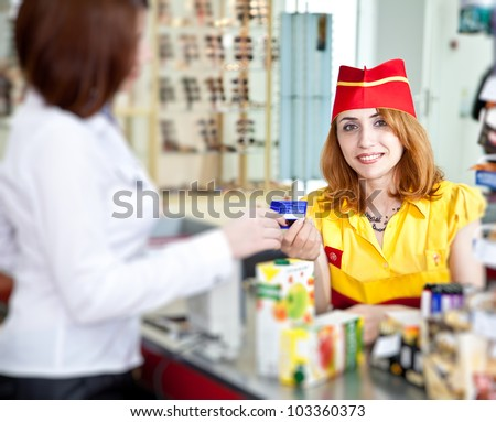 woman doing shopping in supermarket and paying by credit card - stock photo