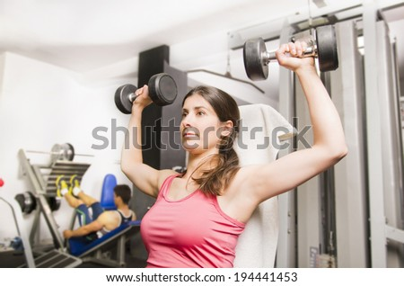 Woman doing shoulder exercise with gym dumbbells - stock photo