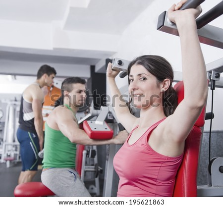 Woman doing shoulder exercise with gym machines - stock photo