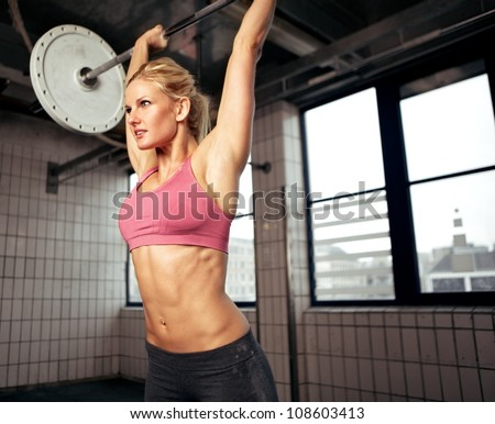 Woman doing shoulder press exercise with a weight bar inside a gym - stock photo