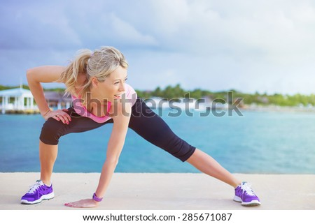 Woman doing stretching exercises before morning workout outdoors - stock photo