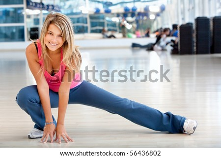 woman doing stretching exercises on the floor at the gym - stock photo