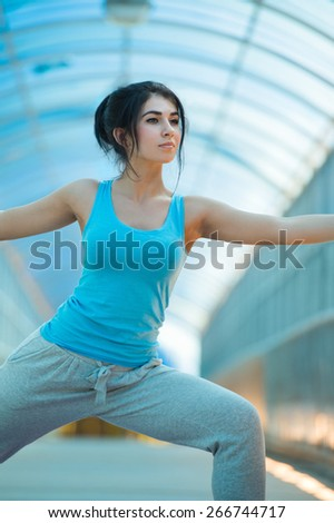 Woman doing stretching yoga exercises outdoors on the bridge.  - stock photo